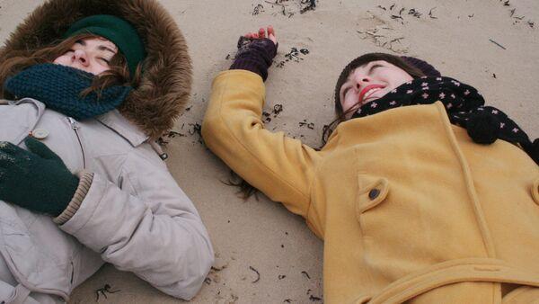 Девушки на пляже в зимней одежде - Sputnik Latvija