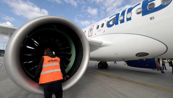 Специалист осматривает самолет Bombardier CS300 в Рижском аэропорту - Sputnik Латвия