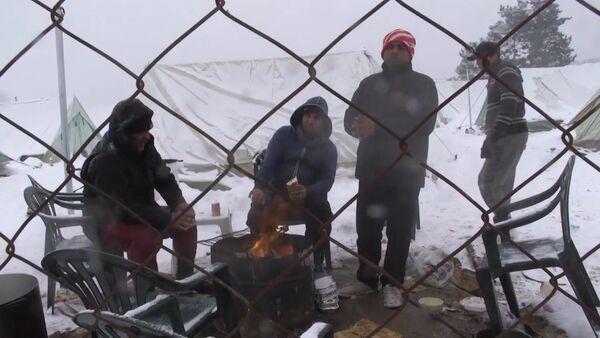 Беженцы грелись у костра в занесенном снегом лагере мигрантов в Салониках - Sputnik Латвия