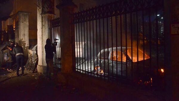 Оператор одного из грузинских телеканалов снимает сожженные в ходе беспорядков в Батуми машины - Sputnik Латвия