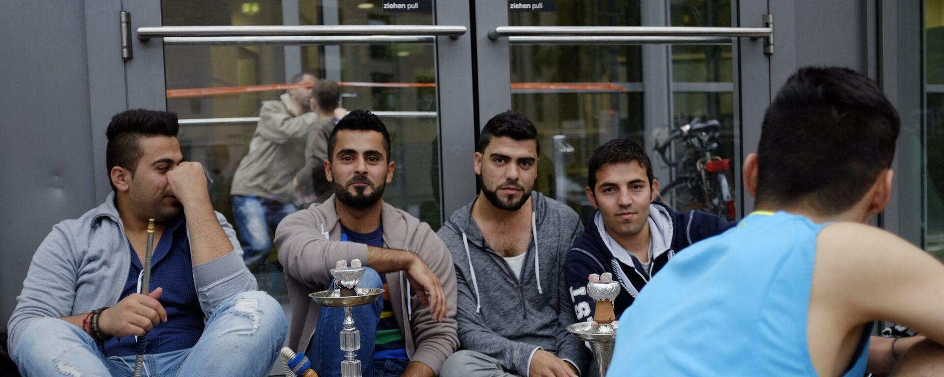 Беженцы с Ближнего Востока у выставочного центра в Гамбурге - Sputnik Латвия, 1920, 29.08.2018