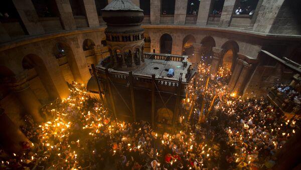 Православные верующие держат свечи во время церемонии в Храме Гроба Господня в Иерусалиме - Sputnik Латвия