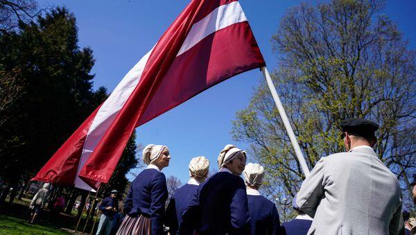 Флаг Латвии у латвийцев в национальных латышских костюмах - Sputnik Латвия