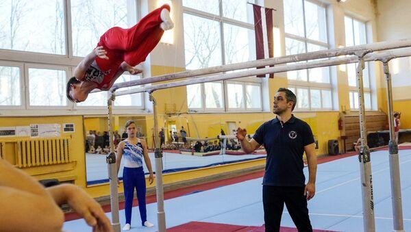 Тренер Рижской гимнастической школы Игорь Вихров наблюдает за воспитанником - Sputnik Латвия