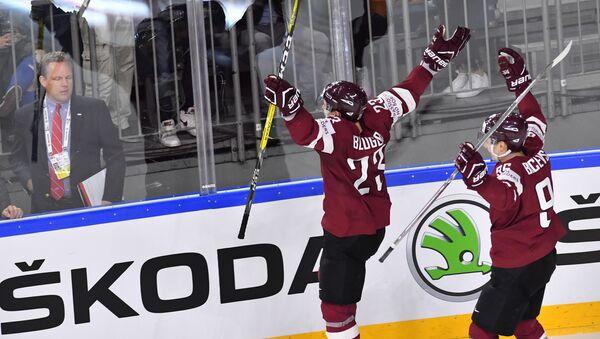 Игрок сборной Латвии Теодор Блюгерс (слева) радуется заброшенной шайбе в матче группового этапа чемпионата мира по хоккею 2017 - Sputnik Латвия