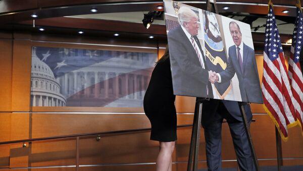 Переговоры за картиной с изображением встречи президента США Дональда Трампа и главы МИД России Сергея Лаврова в Конгрессе США - Sputnik Latvija