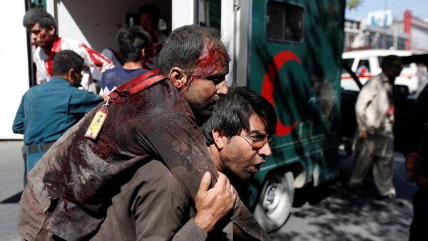 Афганский мужчина несет раненого в больницу после взрыва в Кабуле, Афганистан - Sputnik Латвия