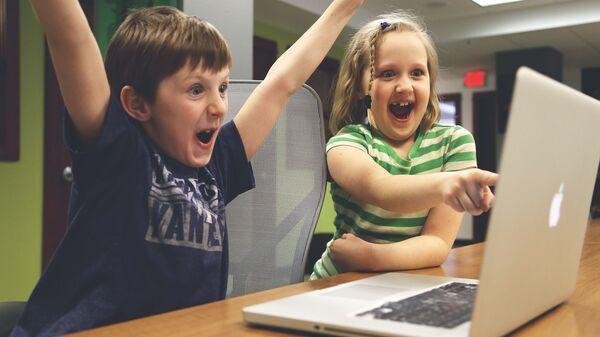 Мальчик с девочкой за ноутбуком - Sputnik Latvija