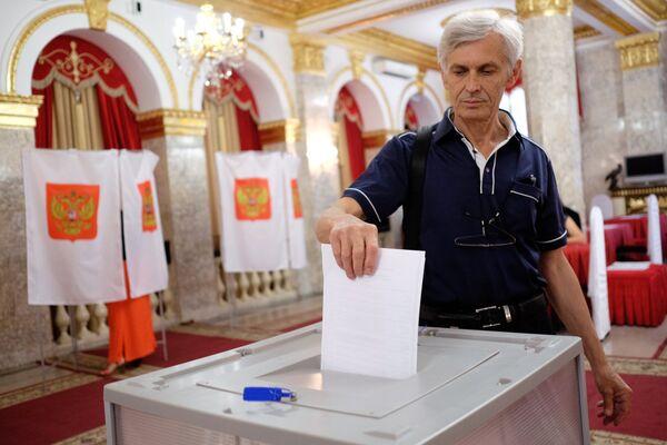 Krasnodaras iedzīvotājs vēlēšanu iecirknī sākotnējās balsošanas laikā partijas Vienotā Krievija kandidātu atlases pasākumā, 2017 - Sputnik Latvija