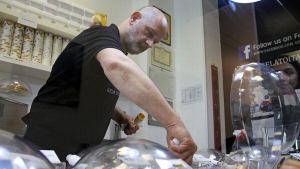 Хозяин кафе Gelato Italia итальянец Дарио Бони за прилавком своего уютного кафе - Sputnik Латвия