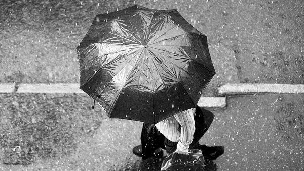 Человек с зонтиком под дождем - Sputnik Латвия