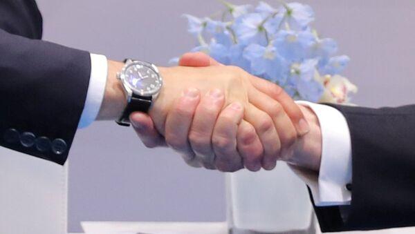 Президент РФ Владимир Путин обменивается рукопожатием с президентом США Дональдом Трампом во время их двусторонней встречи на саммите G20 в Гамбурге - Sputnik Латвия