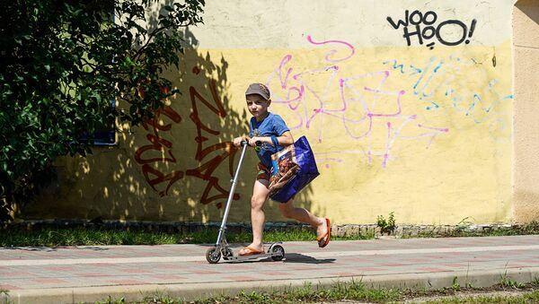 Ребёнок катается на самокате в Лиепаи - Sputnik Латвия