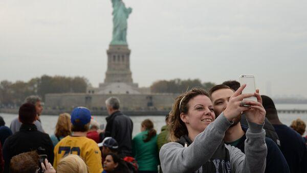 Туристы фотографируются на фоне Статуи Свободы в Нью-Йорке - Sputnik Латвия