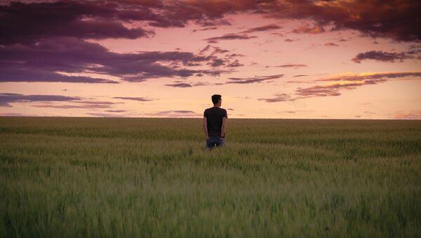 Vīrietis stāv lauka vidū saulrieta laikā - Sputnik Latvija