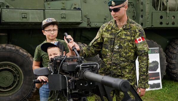 Kanādas karavīrs demonstrē bērniem automātisko granātmetēju - Sputnik Latvija