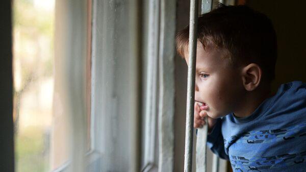 Воспитанник детского дома смотрит в окно - Sputnik Латвия