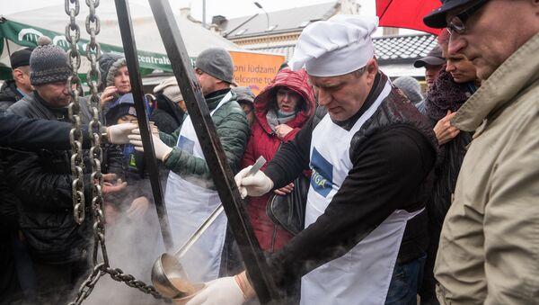 Председатель Комитета городского развития Рижской думы Максим Толстой угощает посетителей праздника душистой ухой - Sputnik Латвия