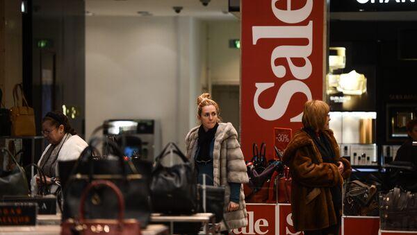 Женщина выбирает сумку во время зимней распродажи - Sputnik Латвия