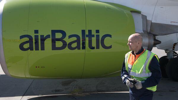 Сотрудник аэропорта Шереметьево радом с самолетом Bombardier CS300 латвийской авиакомпании airBaltic - Sputnik Латвия