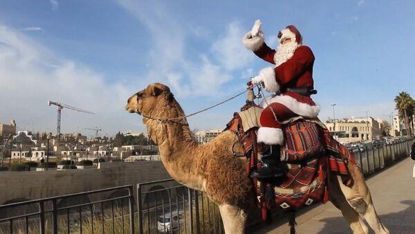 Санта-Клаус верхом на верблюде в Восточном Иерусалиме - Sputnik Латвия