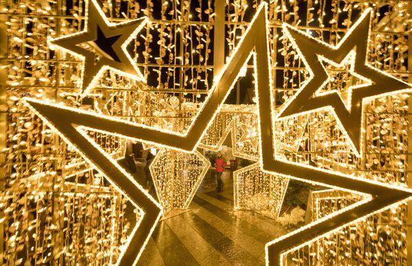 A man walks by a large Christmas decoration panel at the Christmas market in Sankt Poelten, Austria - Sputnik Latvija