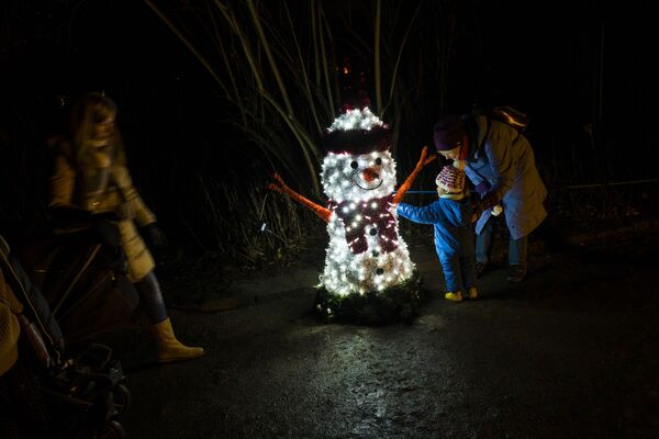 A toddler touches a snowman made of lights at the Christmas Garden light show, in Berlin's botanical garden - Sputnik Latvija