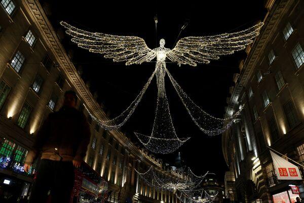 A man walks beneath Christmas street lights on Regent Street in London, Britain - Sputnik Latvija
