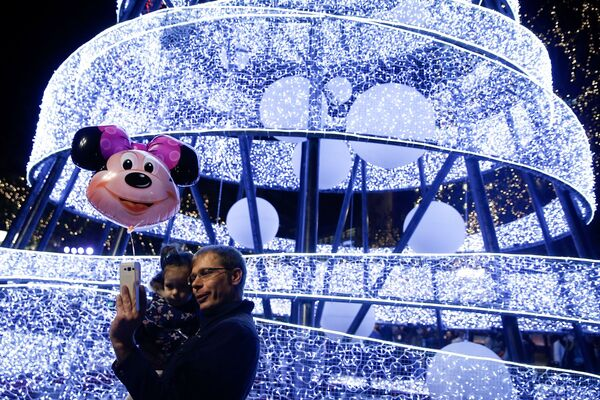 A man takes a selfie as he holds his child during a Christmas tree lighting ceremony at central Syntagma square in Athens, Greece - Sputnik Latvija