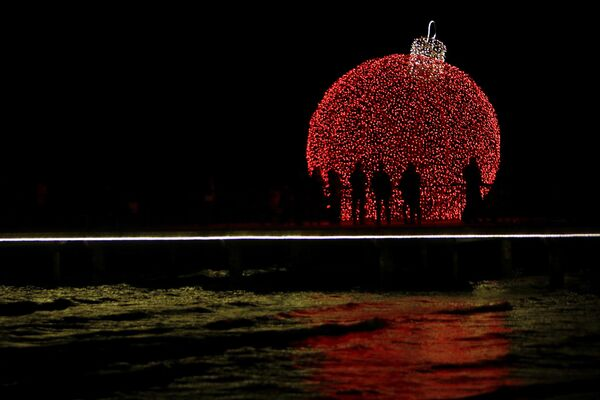 People are silhouetted on a pedestrian dock decorated with an illuminated Christmas ornament in the southern coastal city of Larnaca on the eastern Mediterranean island of Cyprus - Sputnik Latvija