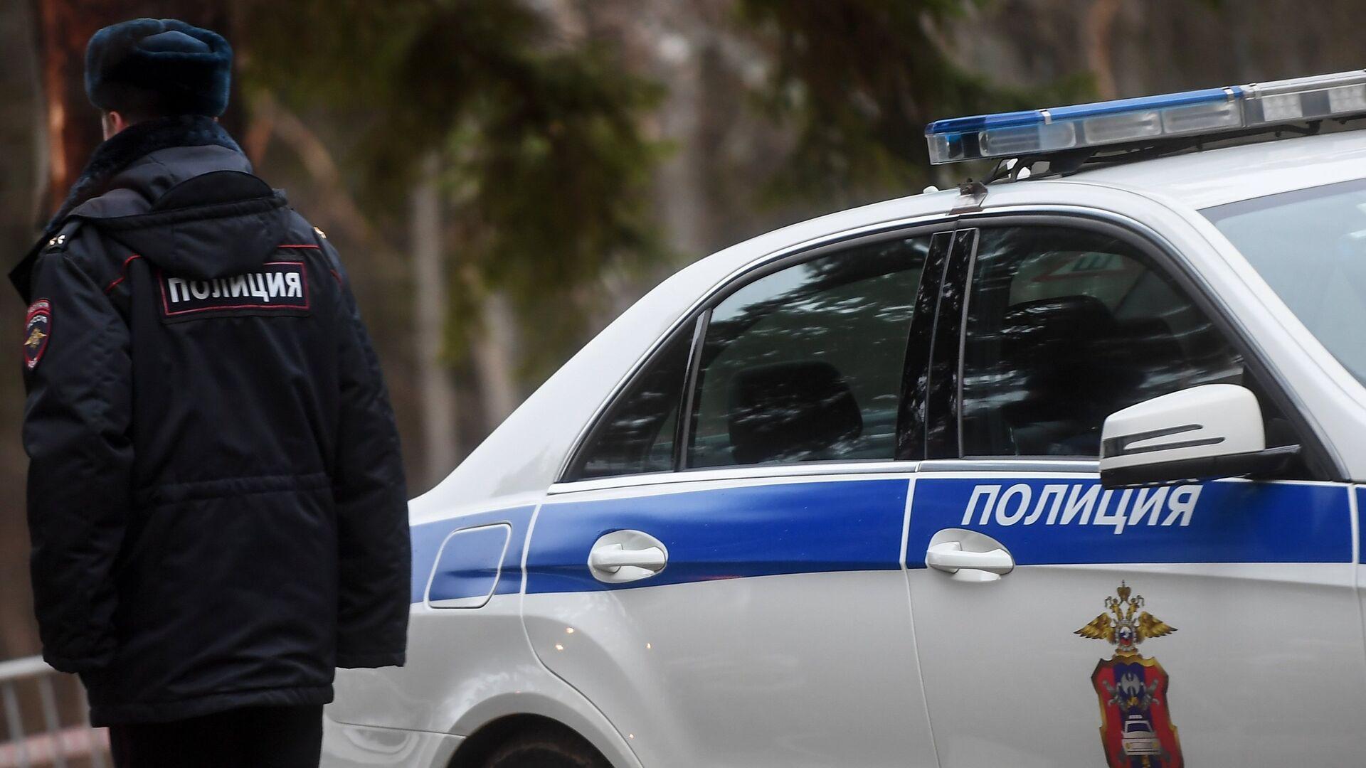 Сотрудник полиции возле служебного автомобиля - Sputnik Латвия, 1920, 07.09.2021