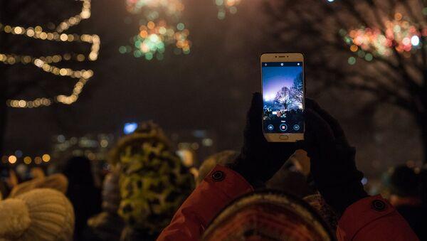 Женщина снимает на телефон Новогодний салют - Sputnik Латвия