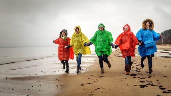 Девушки в дождевиках на пляже Юрмалы - Sputnik Латвия