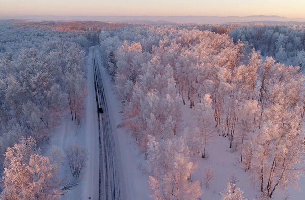 Mašīna uz šosejas sniega klāta meža malā saulrietā, Krasnojarskas novads - Sputnik Latvija