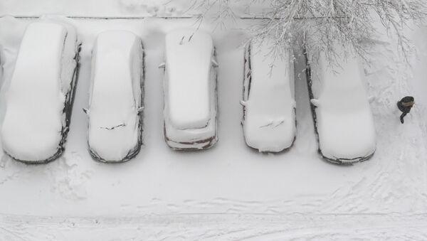 Женщина идет мимо занесенных снегом машин во время снегопада - Sputnik Latvija