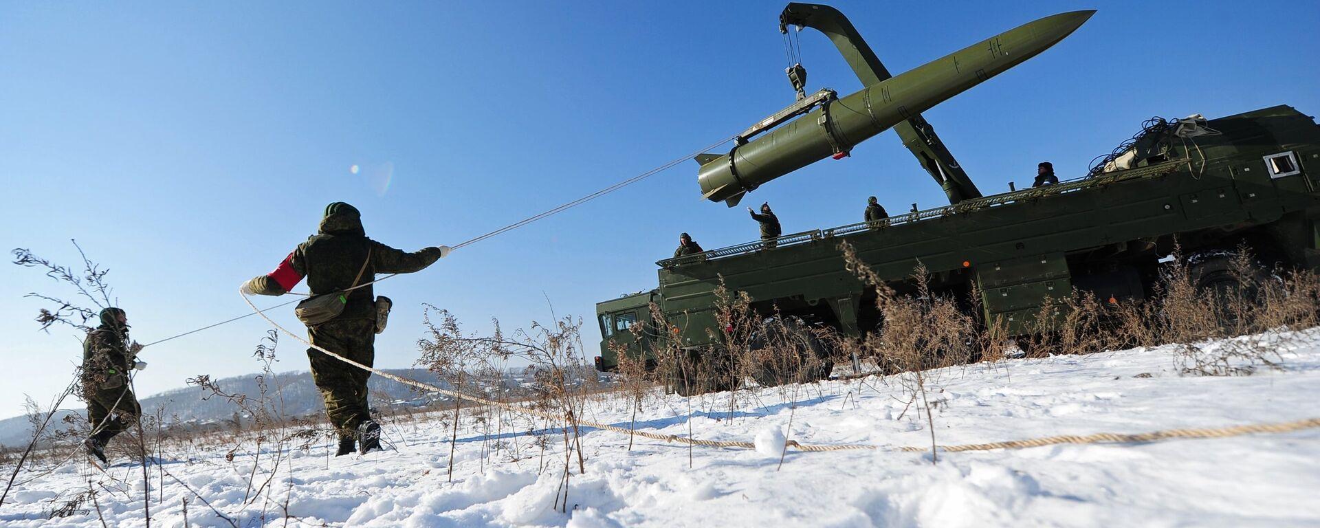 Военнослужащие ВС РФ контролируют загрузку ракеты транспортно-заряжающий машиной на самоходную пусковую установку оперативно-тактического ракетного комплекса Искандер-М - Sputnik Latvija, 1920, 11.03.2021