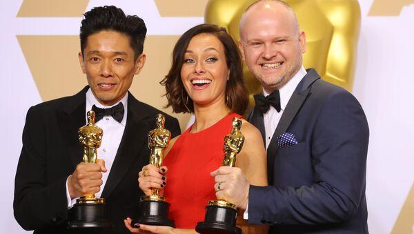 Kacuhiro Cudzi, Lūsija Sibika un Deivids Maļinovskis ar Oskara statuetēm par labāko grimu un frizūrām filmā Tumšie laiki. - Sputnik Latvija
