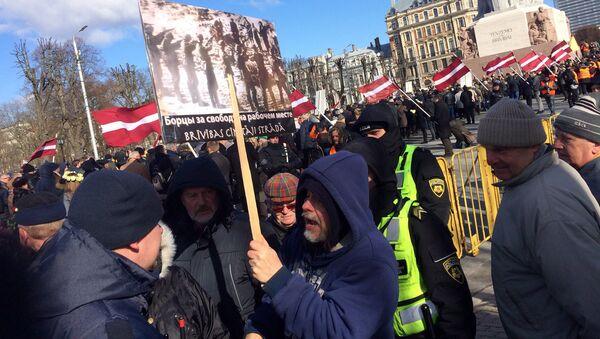 Иностранец с антинацистским плакатом, задержанный на шествии легионеров СС в Риге - Sputnik Латвия