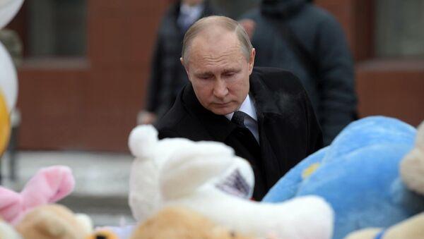 Президент РФ Владимир Путин возлагает цветы к стихийному мемориалу у торгового центра Зимняя вишня в Кемерово, где случился пожар - Sputnik Латвия