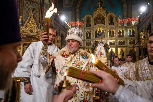 Митрополит Рижский и всея Латвии Александр с Благодатным огнем, привезенным из Иерусалима - Sputnik Латвия