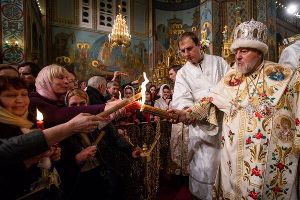 Митрополит Рижский и всея Латвии Александр раздает верующим Благодатный огонь, привезенный из Иерусалима - Sputnik Латвия