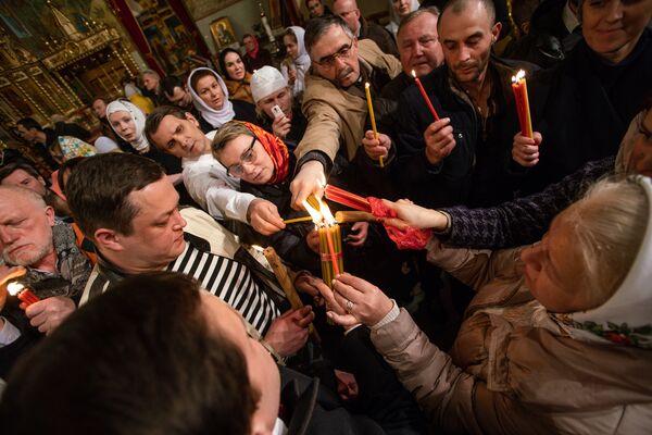 Православные христиане делятся Благодатным огнем, привезенным из Иерусалима - Sputnik Латвия