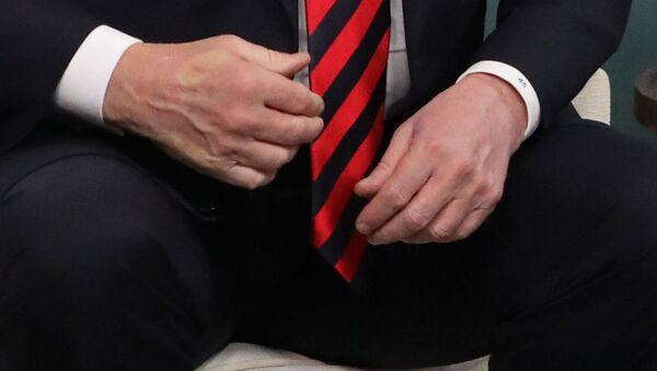 Отпечаток пальца французского президента Эммануэля Макрона на руке президента США Дональда Трампа после того, как они обменялись рукопожатием во время двусторонней встречи на саммите G7 в Шарлеоике, Квебек, Канада. 8 июня 2018 - Sputnik Latvija
