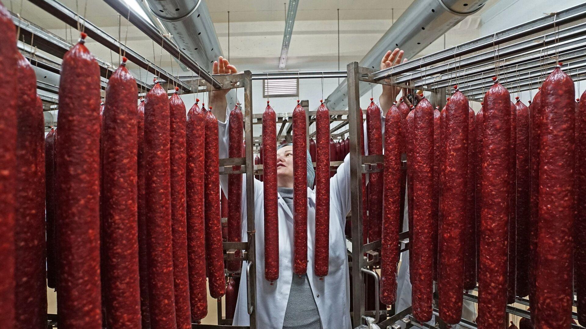 Сотрудник во время производства мясных деликатесов - Sputnik Латвия, 1920, 09.07.2021