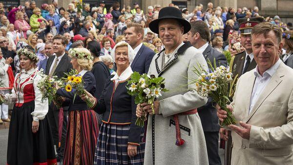 Президент Латвии Раймондс Вейонис с супругой, одетые в народные костюмы, во время шествия участников Праздника песни и танца - Sputnik Латвия