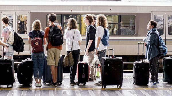 Молодые люди на станции железнодорожного вокзала - Sputnik Латвия