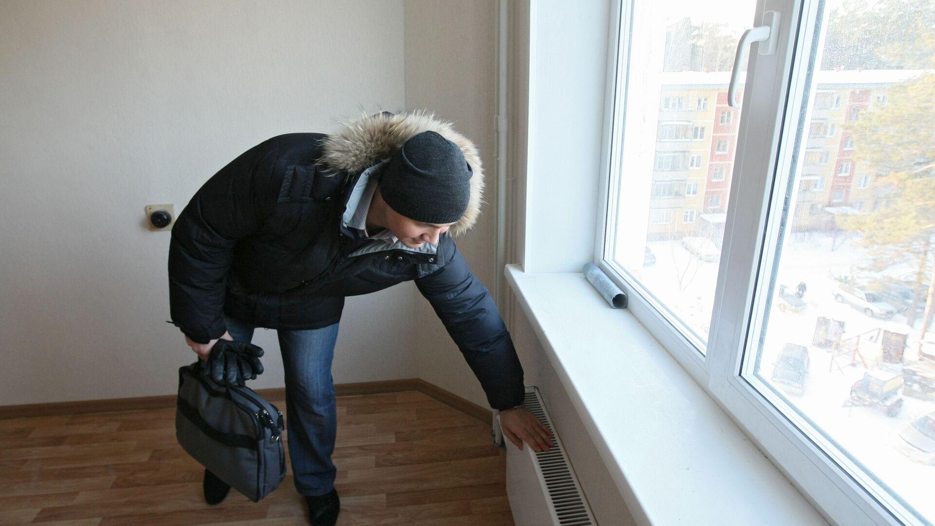 Мужчина проверяет систему отопления - Sputnik Латвия, 1920, 17.02.2021