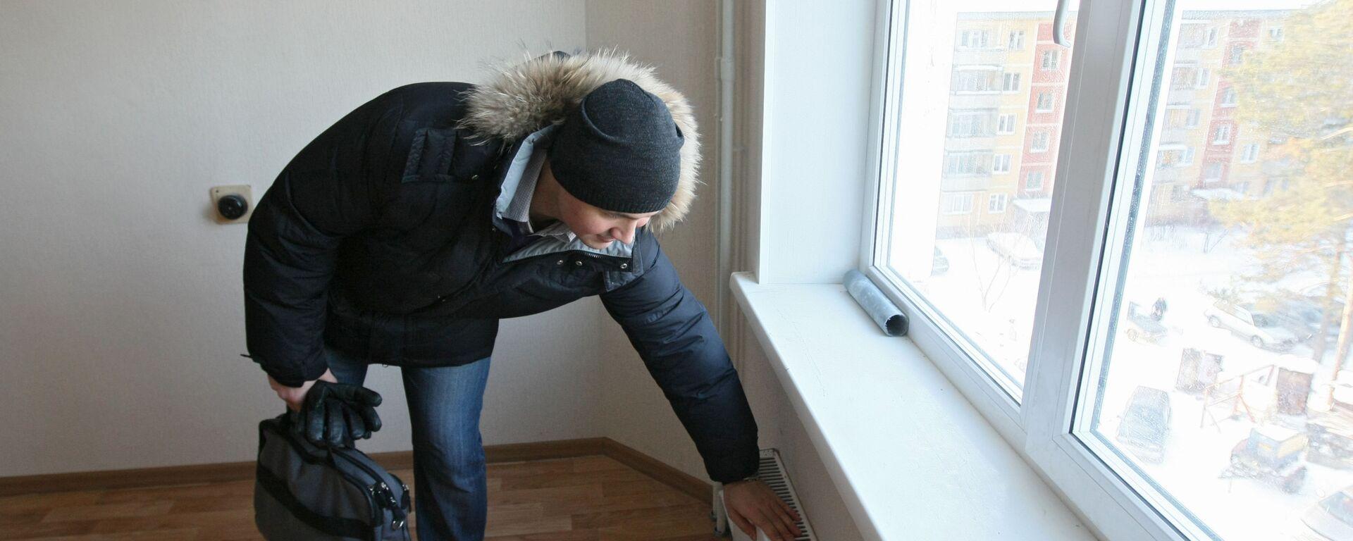 Мужчина проверяет систему отопления - Sputnik Latvija, 1920, 18.02.2021
