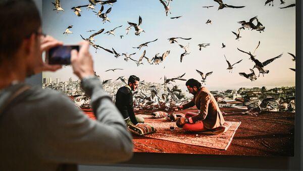 Посетитель на открытии выставки победителей IV международного конкурса фотожурналистики имени Андрея Стенина в Москве - Sputnik Латвия